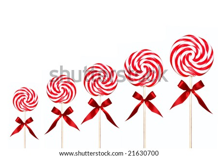 Holiday Candy Swirl Lollipops In A Line on White Background With Red Bow - stock photo