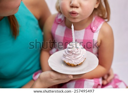 holiday, celebration, family, birthday and people concept - happy mother holding cupcake and little girl blowing out candle - stock photo