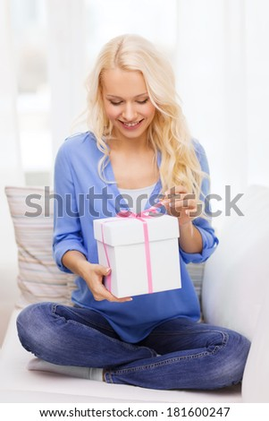 holiday, celebration, home and birthday concept - smiling young woman with gift box at home - stock photo
