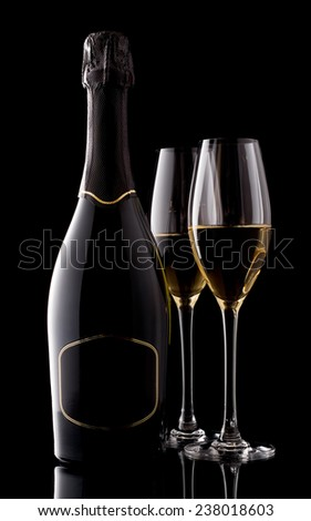 Holiday champagne bottle and two champagne glass on a black - stock photo