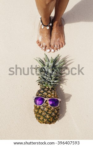 Holiday concept. Pineapple with sunglasses in a  Caribbean beach - stock photo