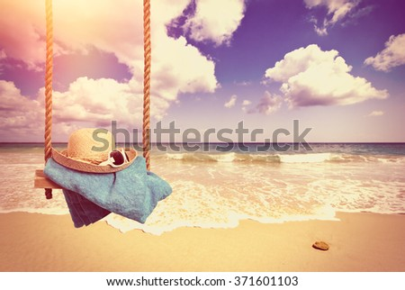 Holiday concept with idyllic beach scene with sunhat and glasses on swing - vintage tone effect for a nostalgic feel - stock photo