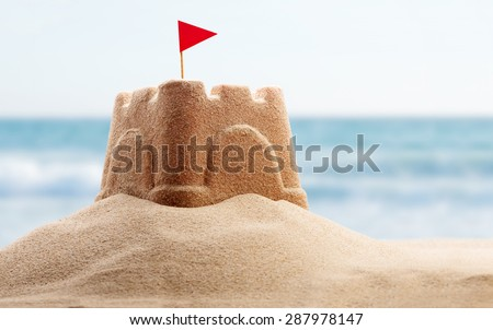 Holiday concept with sandcastle on the seaside - stock photo