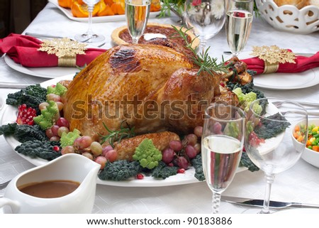 Holiday-decorated table, Christmas tree, champagne, and roasted turkey. - stock photo