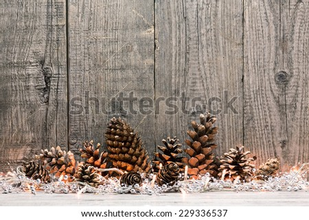 Holiday decoration with Christmas lights and cones over wooden background - stock photo