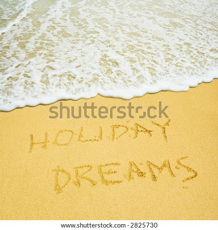holiday dreams written in the sandy beach - stock photo