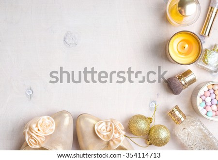 Holiday feminine cosmetic background in gold colour. Cosmetic objects: gold heels, christmas balls, glitter nail polish, perfume, burning candle, meteorites blush, brush. Getting ready for a party - stock photo