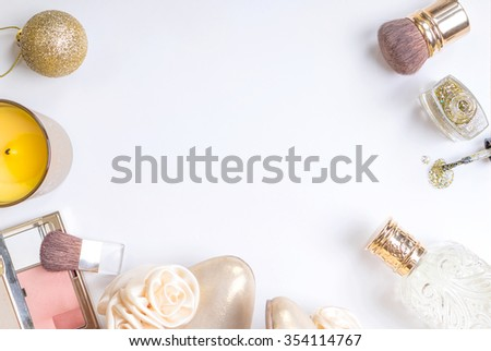 Holiday feminine cosmetic background in gold colour. Cosmetic objects: gold heels, christmas balls, glitter nail polish, perfume, burning candles, blush, lip gloss, brushes. Getting ready for a party - stock photo