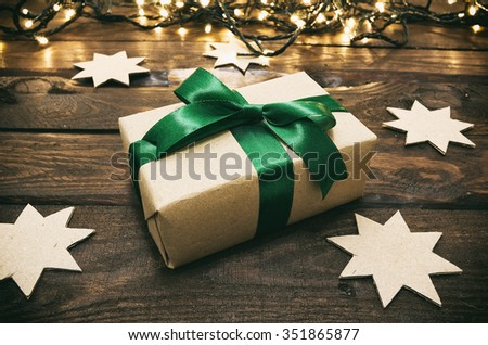 Holiday gift box with green bow on aged brown wood background with cardboard crafted cut stars and warm christmas lights. - stock photo
