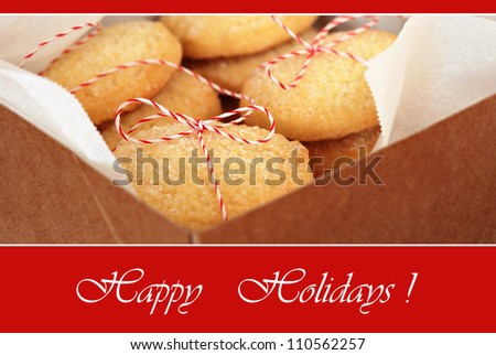 Holiday greeting card with macro image of sugar cookies tied with festive bakers twine in box.  Shallow dof with selective focus on string bow. - stock photo