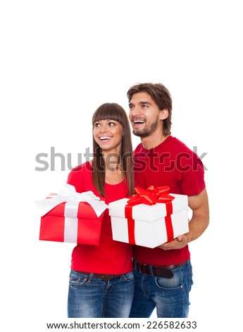 holiday happy couple hold present gift box wear red shirt looking side, man and woman love smile embracing, isolated over white background - stock photo