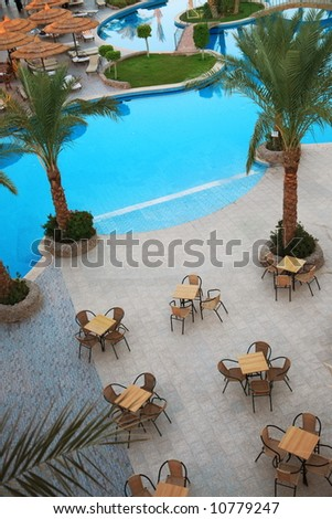 Holiday hotel and beautiful swimming pool with cafe and palms - stock photo