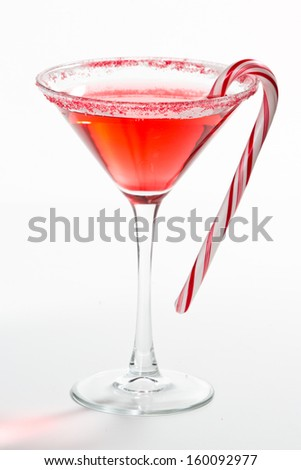 Holiday martini isolated on a white background with a red and white sugar rim - stock photo