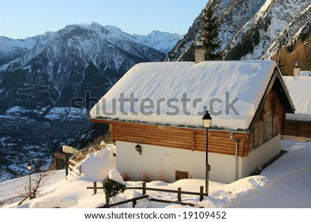Holiday mountain house covered by snow in Tschuggen, Wallis, Switzerland - stock photo