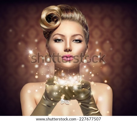 Holiday Retro Woman blowing magic dust in her hand. Beauty Fashion Christmas Vintage Style Lady with Beautiful Luxury Hairstyle, makeup, accessories. Golden Silk Gloves and dress  - stock photo