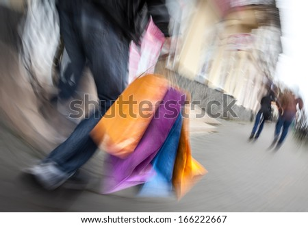Holiday sales. Man with many shopping bags in his hand. Intentional motion blur - stock photo