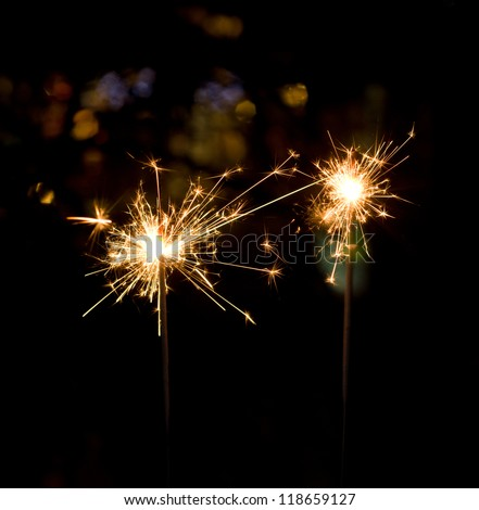 Holiday sparklers on colorful bokeh background - stock photo