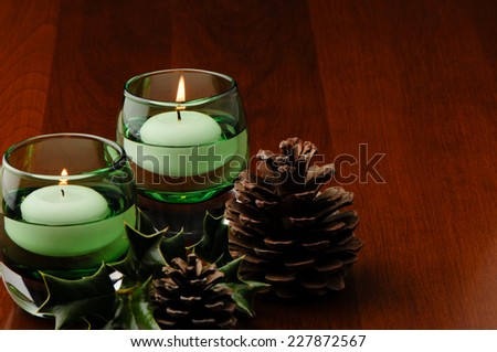 Holiday Table Decoration Candles Pine Cones Holly - stock photo