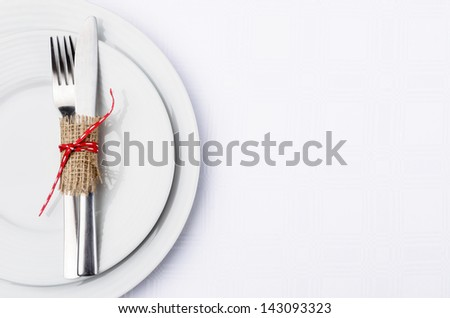 Holiday table setting with cutlery tied in hessian and red ribbon on white table cloth - stock photo