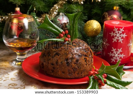 Holiday table with Christmas pudding decorated with holly twig, glass of brandy, ornaments, candles, and xmas tree.  - stock photo
