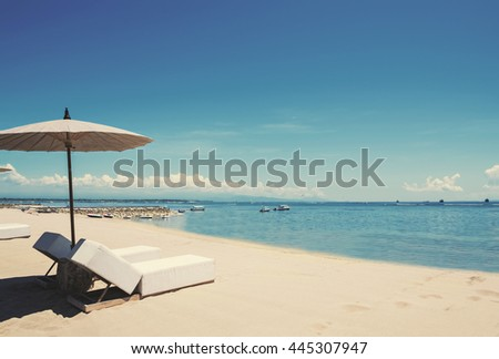 Holiday vacation at the beach, Beach deck chairs with parasol on tranquil beach  - stock photo