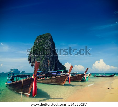 Holiday vacation concept background - Long tail boat on tropical beach with limestone rock, Krabi, Thailand. Cross process version - stock photo