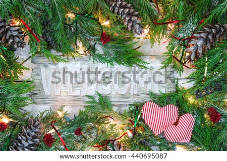 Holiday welcome sign with green Christmas tree garland border, candy cane striped hearts, snow and lights on antique rustic wooden background - stock photo