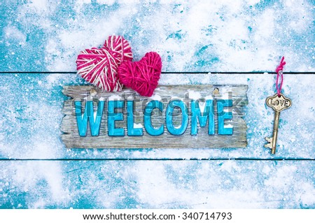 Holiday winter welcome sign with pink rope heart and skeleton key on antique rustic teal blue snowy background - stock photo