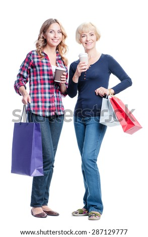 Holiday with mother. Family shopping. Portrait of smiling caucasian middle aged woman and her adult daughter holding bags. Isolated on white. - stock photo