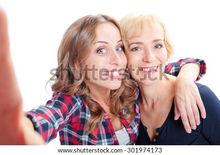Holiday with mother. Portrait of smiling caucasian middle aged woman and her adult daughter taking selfie. Isolated on white. - stock photo