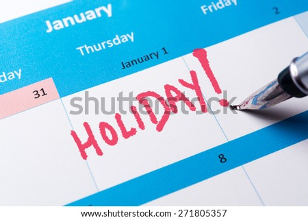 Holiday word written on the calendar with a pen - stock photo