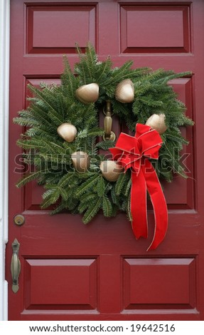 holiday wreath with gold shells and red bow - stock photo