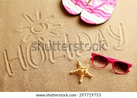 Holiday written in sand at the beach - stock photo