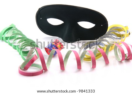 holidays and party time paper streamers party blower and black mask isolated on white background - stock photo
