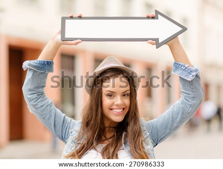 holidays and tourism concept - beautiful girl showing direction with arrow in the city - stock photo