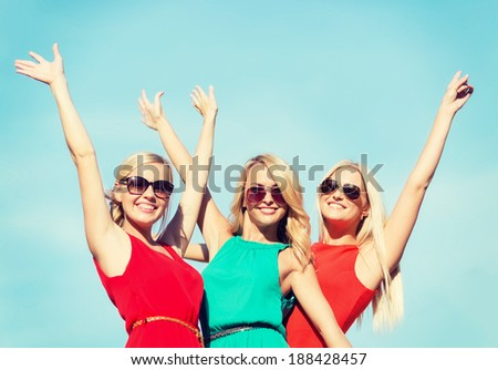 holidays and tourism, friends, hen party, blonde girls concept - three beautiful women waving hands over sky background - stock photo