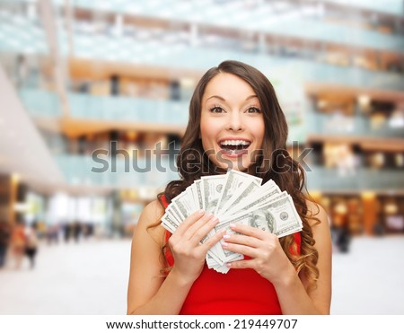 holidays, banking, winning and people concept - smiling woman in red dress with us dollar money over shopping centre background - stock photo