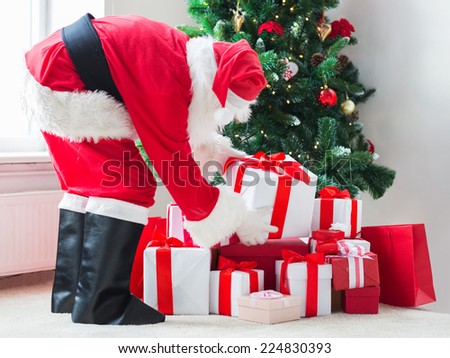 holidays, celebration and people concept - man in costume of santa claus putting present under christmas tree - stock photo
