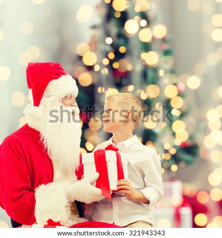 holidays, childhood and people concept - smiling little boy with santa claus and gifts over christmas tree lights background - stock photo