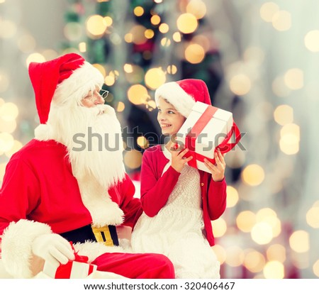 holidays, childhood and people concept - smiling little girl with santa claus and gifts over christmas tree lights lights background - stock photo