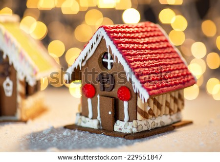 holidays, christmas, baking and sweets concept - closeup of beautiful gingerbread houses on table over lights background - stock photo