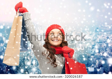 holidays, christmas, x-mas, sale and people concept - happy young asian woman in winter clothes with shopping bags over snow and city background - stock photo