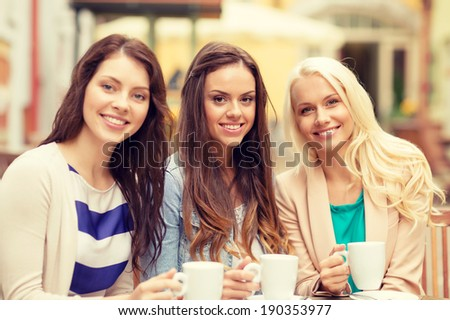 holidays, food and tourism concept - three beautiful girls drinking coffee in cafe - stock photo