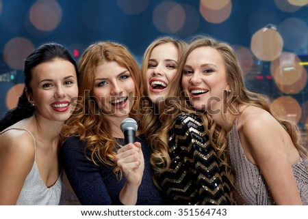 holidays, friends, bachelorette party, nightlife and people concept - three women in evening dresses with microphone singing karaoke over lights background - stock photo