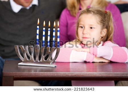 Holidays: Little Girl Looks At Hanukkah Candles - stock photo