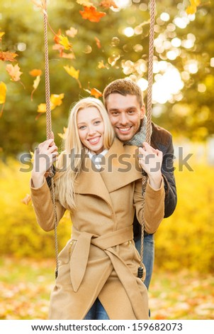 holidays, love, travel, tourism, relationship and dating concept - romantic couple in the autumn park - stock photo