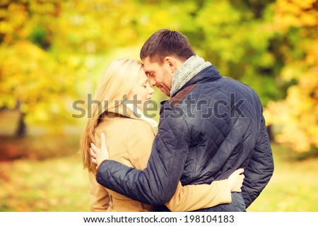 holidays, love, travel, tourism, relationship and dating concept - romantic couple kissing in the autumn park - stock photo