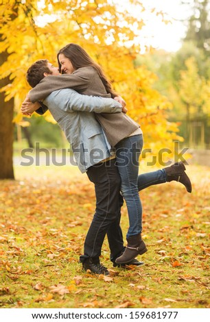 holidays, love, travel, tourism, relationship and dating concept - romantic couple playing in the autumn park - stock photo