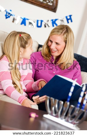 Holidays: Mother And Daughter Reading Hanukkah Story Together - stock photo