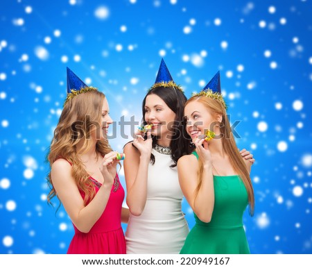 holidays, people and celebration concept - smiling women in party caps blowing to whistles over blue snowing background - stock photo